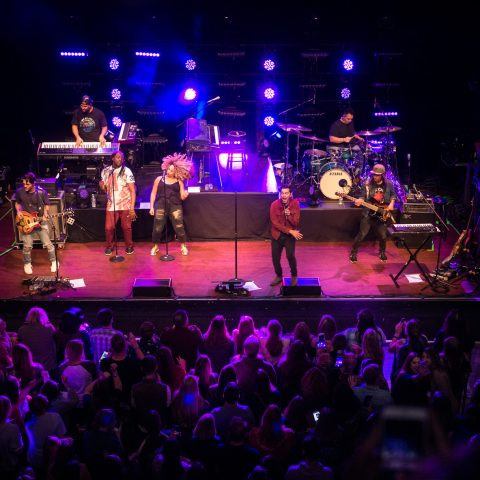 Band plays on lit stage to large audience of people at indoor venue