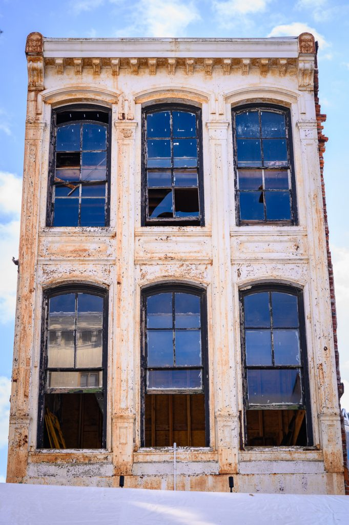Tall, weathered building with large windows against a blue sky