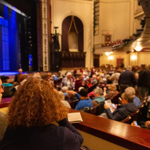 A packed audience in a gorgeous, old theater waiting for a show to begin at the Playhouse on Rodney Square
