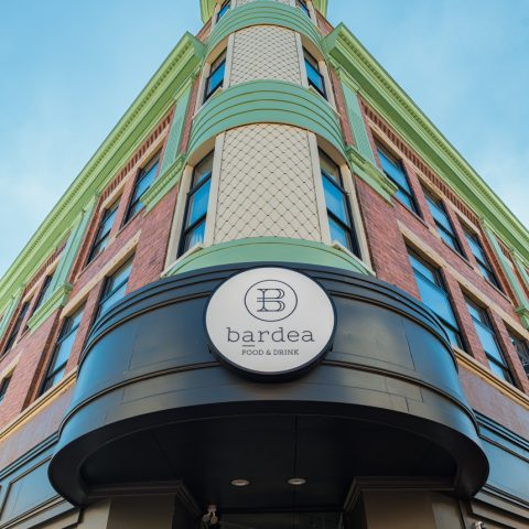 Exterior of tall art-deco building with green trim and a Bardea Food & Drink sign