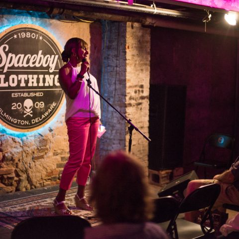 Woman speaks in to microphone on small stage in front of audience in folding chairs at Spaceboy Clothing