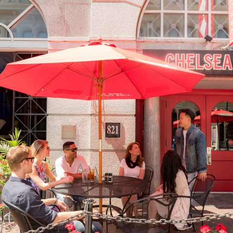 Group of friends sitting at outdoor table under umbrella outside of Chelsea Tavern
