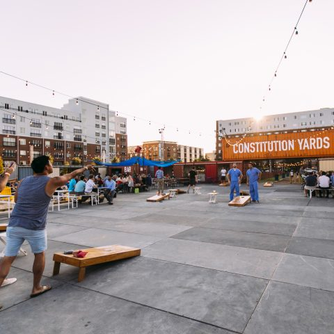 Rooftop courtyard with picnic tables and group playing cornhole under string lights with Constitution Yards sign