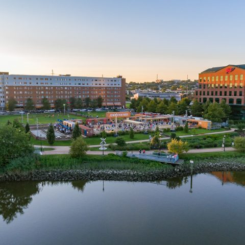 Golden hour over Constitution Yards next to river with lush greenery