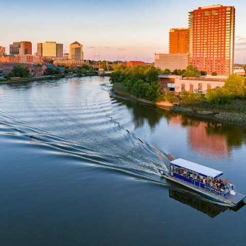 Riverfront cruise boat on water sailing past city landscape
