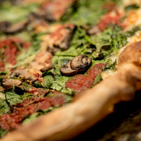 Close-up view of a veggie pizza with crispy crust, mushrooms, and spinach
