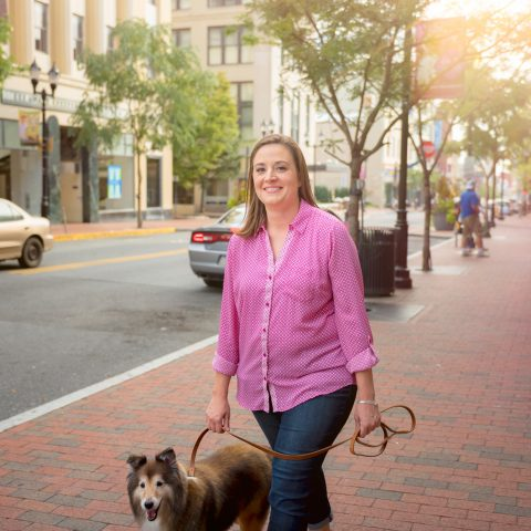 A woman smiling and walking her dog along a cobblestone sidewalk next to a city street