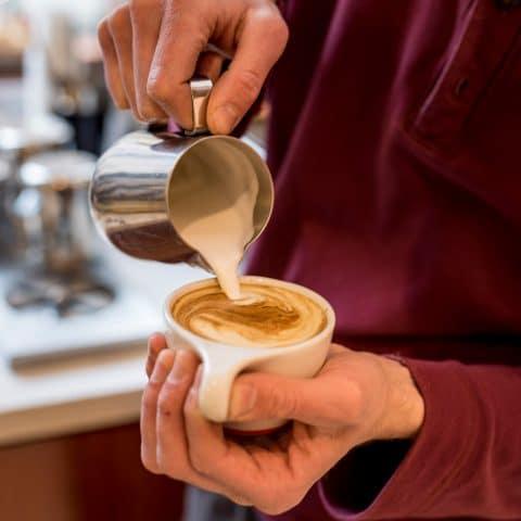Barista pours cream in a swirly design into small coffee cup