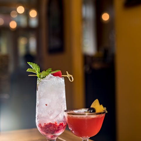 A small pink cocktail next to a tall white drink with crushed fruit in the bottom, both adorned with fruit garnish