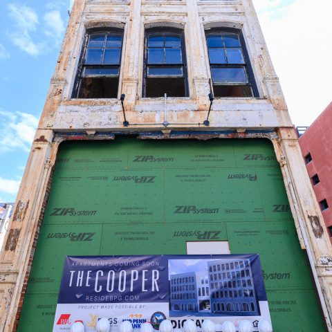 Tall building on construction with shovels outside and a sign for The Cooper