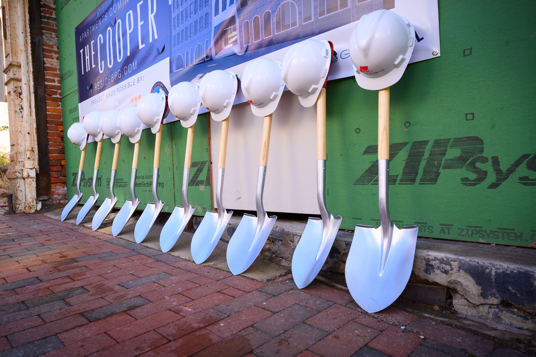 Hardhats leaning on shovels at The Cooper development site