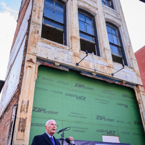 Man stands at podium giving speech outside of apartment building in development