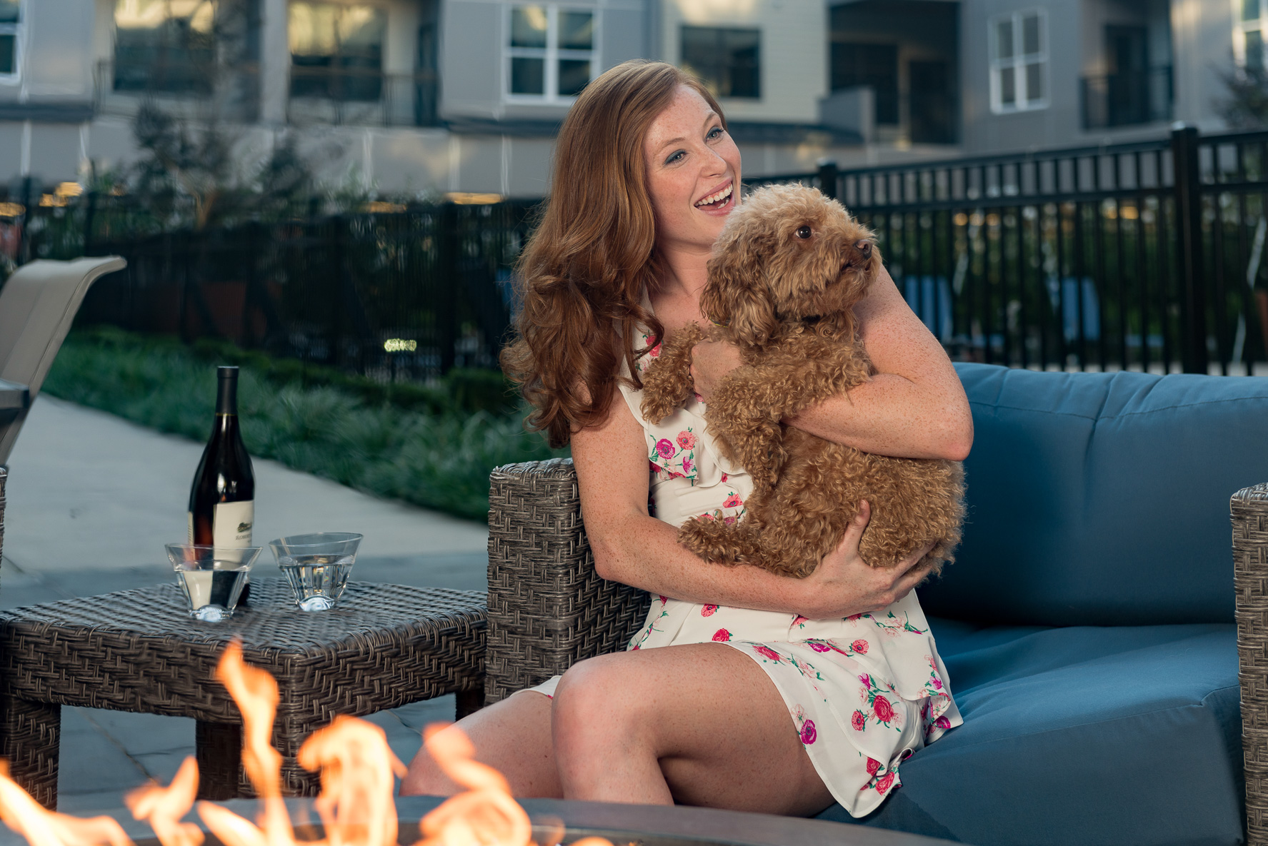Woman laughing and holding small, fluffy dog in front of outdoor fireplace