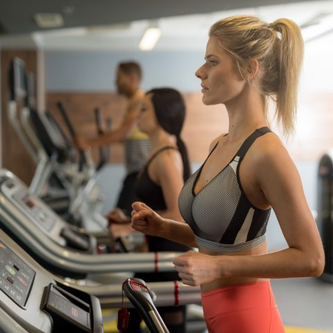 Woman with blonde hair in brightly colored workout clothes runs on treadmill