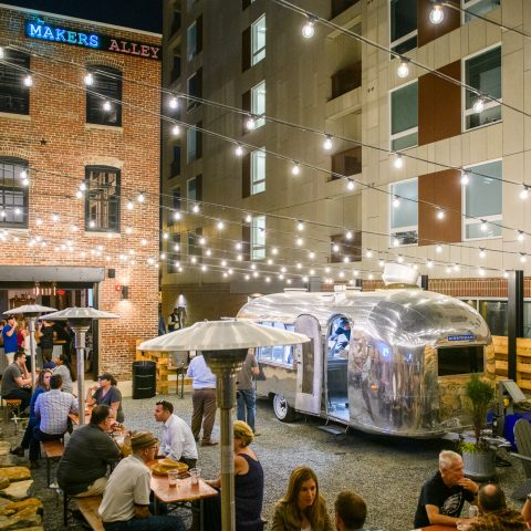 Makers Alley in the evening with outdoor picnic tables, an old metal camper, and a garage door entrance into a bar