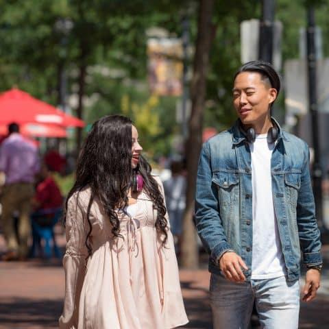 Couple in conversation walking on city sidewalk