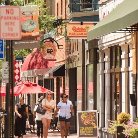 City sidewalk view of restaurants and shopfronts