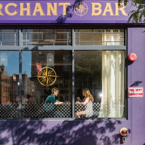 Exterior of purple and yellow Merchant Bar with windows looking in on a man and woman at a table