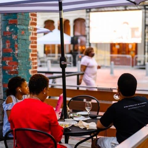 A family enjoys a meal at an outdoor table under an umbrella