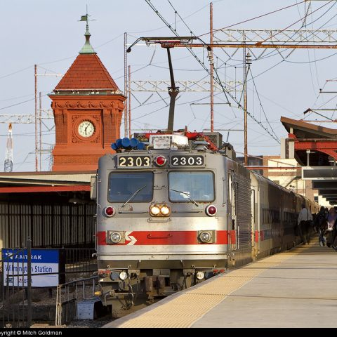 Amtrak train pulling in to station in Wilmington, DE with red clock tower in background