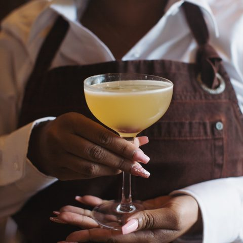 Waitress with brown apron and mask on holds yellow cocktail