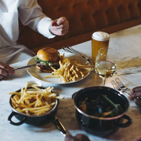 Restaurant table with full wine glass and beer glass and a plate of burger and fries